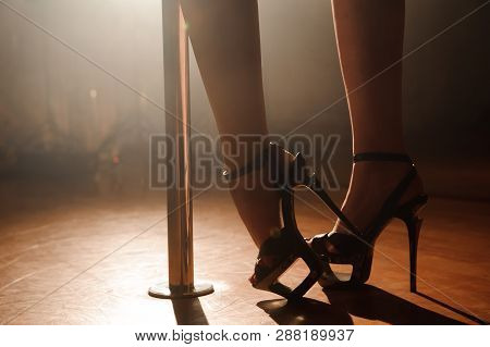 Pole Dancer, Legs Near Pylon. An Attractive Sexy Woman Pole Dancer Performing.