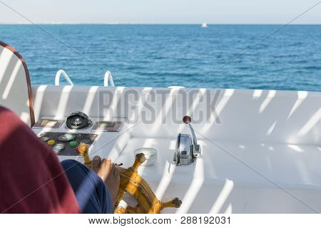 People At The Helm Of A White Yacht. A Man Arab Controls The Yacht. Foot On The Yacht Steering Wheel