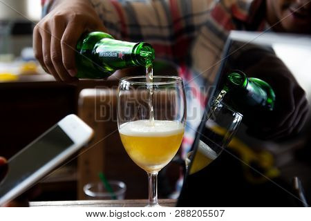 Bangkok, Thailand - August 19, 2018 : Business Man Pouring Heineken Beer Into Glass On Table With La