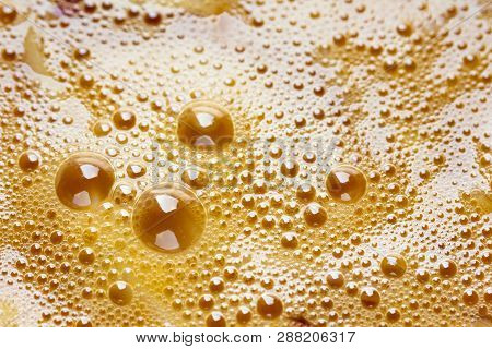 Abstract Orange Background Of Fresh Chicken Egg Yolks Surface With Bubbles Texture. Breakfast Cookin