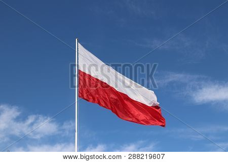 White-red Horizontal Flag On A Flagpole Developing In The Wind Against A Blue Sky With Light Clouds.