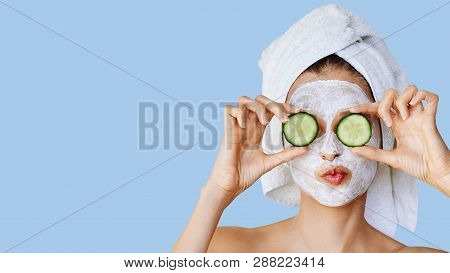 Beautiful Young Woman With Facial Mask On Her Face Holding Slices Of Fresh Cucumber. Skin Care And T