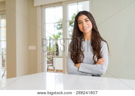 Young beautiful woman at home happy face smiling with crossed arms looking at the camera. Positive person.