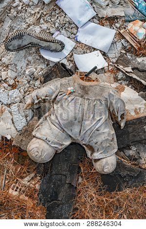 Body Of A Doll Without A Head Distressing Lying In A Landfill With Other Waste.
