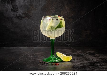 Glass Of Gin Tonic With Mint, Lime And Ice On Dark Background