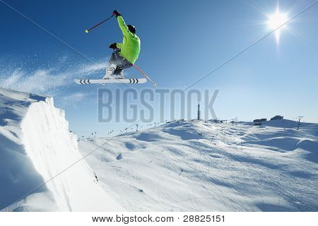 Young skiing man - skier at jump in beautiful alpen snow paradise