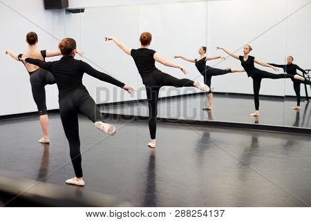 Female Students At Performing Arts School Rehearsing Ballet In Dance Studio Reflected In Mirror