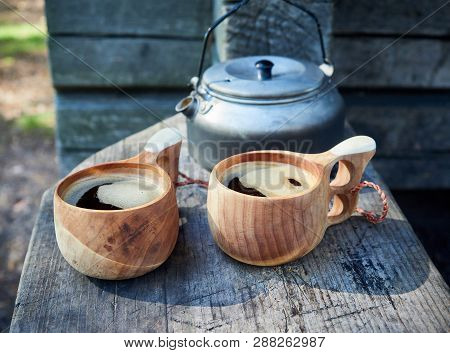 Two Wooden Mugs Filled With Hot Fresh Coffee On The Campsite While Trekking.