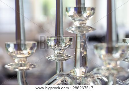 Detail Of Glass Candelabra With Silver Candles. Blurry Background.