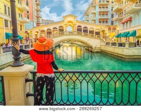 Woman Standing On Balcony Looking Famous Bridge Of Venice, Doha Qatar, At Twilight. Caucasian Touris