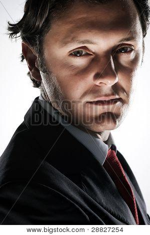 Serious, devious looking businessman in studio