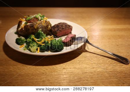 Steak and Potato Dinner with Broccoli with Cheese. On a white plate on a wooden table top. Dinner or Lunch menu.