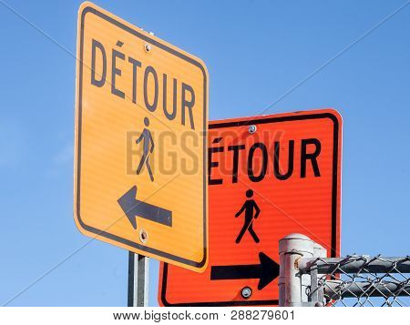 poster of Two Detour road signs, orange color, complying with North American rules indicating a deviation for pedestrians in a street of Montreal, Quebec, Canada