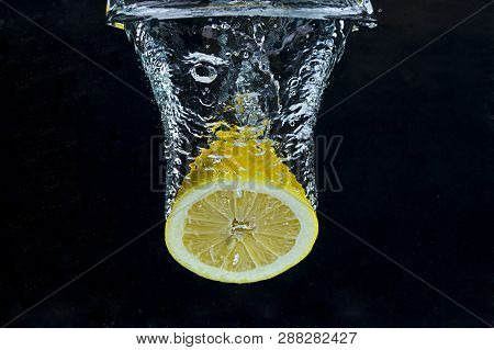 Lemon half plunged into water. A lemon half is plunged into water against a black background. poster