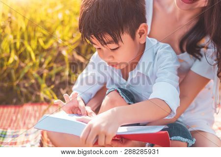 Little Asian Boy And His Mother Reading Tale Story Books At Meadow Field. Mother And Son Learning To