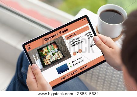 Man Hands Holding Tablet Computer With App Delivery Food On The Screen And Drinking Coffee