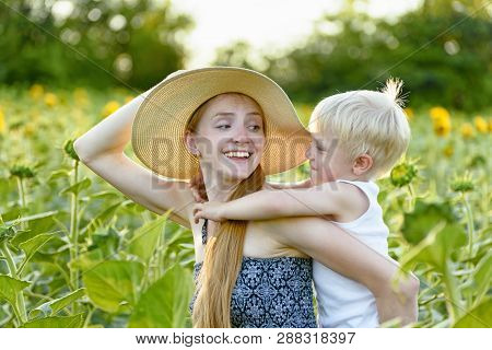 Happy Laughing Mother Giving Toddler Son Piggyback Ride On Background Of Green Blooming Sunflowers F