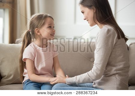 Loving Mother And Child Holding Hands Talking Sitting On Sofa