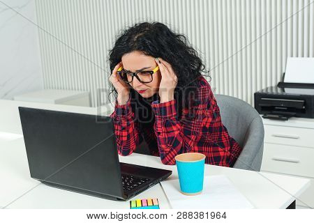 Tired Business Woman At Workplace. Stressed Woman Working On Laptop In Modern Office. Woman Holding