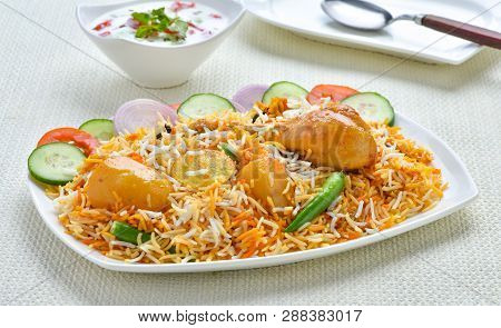 Chicken Biryani. A Deleciously Colorful Rice Dish Filled With Spicy Marinated Chicken Along With Sal