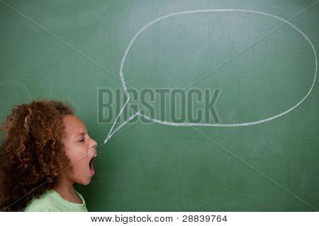 Schoolgirl screaming a speech bubble in front of a blackboard