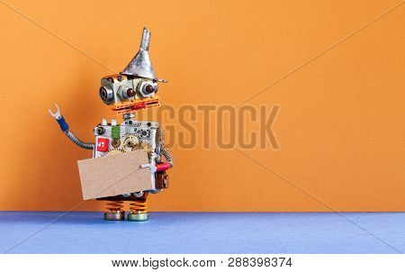Robot Holds A Cardboard Card Mockup. Creative Design Robotic Toy With Blank Empty Paper Poster, Dark
