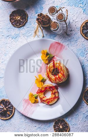 Few Puff Pastry Donuts With Strawberry Topping On White Plate