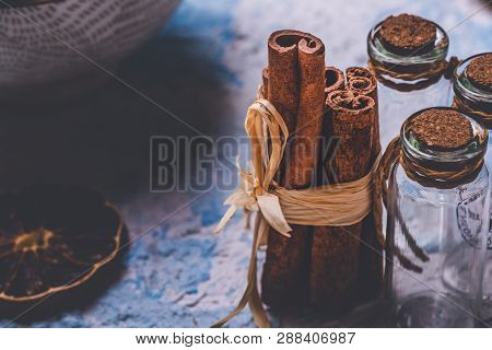 Few Cinnamon Sticks And Small Glass Bottles On Light Wooden Board