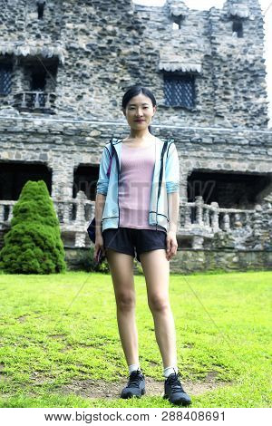 A Chinese Woman Wearing Shorts Standing In Front Of Gillette Castle In East Haddam Connecticut In Ne