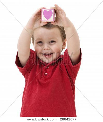 smiling child holding a heart shaped block
