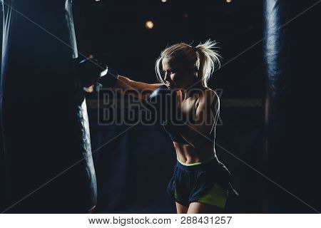 Concept Female Sport. Strong Athletic Young Blond Woman Is Training Self-defense Punches In Boxing G
