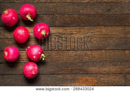 Red, Raw, Whole Radishes Laid Out In The Shape Of A Circle On Dark Brown Wooden Table. Copy Space In