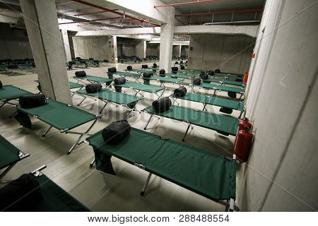 Camp Folding Cots And Sleeping Bags Are Being Set Up In The Underground Parking Of A Stadium And Wai