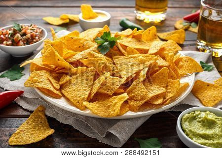 Tortilla Nachos Chips With Cheese Sauce, Guacamole And Tomatoes Salsa Dip. Glass Of Beer.