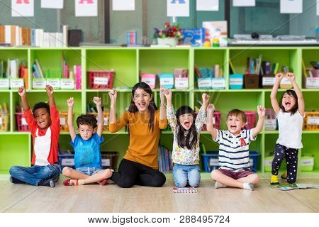 Happy Asian Female Teacher And Mixed Race Kids In Classroom,kindergarten Pre School Concept