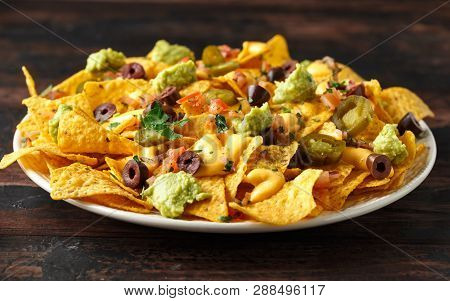 Mexican Nachos Tortilla Chips With Olives, Jalapeno, Guacamole, Tomatoes Salsa And Cheese Dip. Close