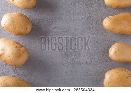 Pile Of Raw Potatoes In The Bowl On Concrete Background