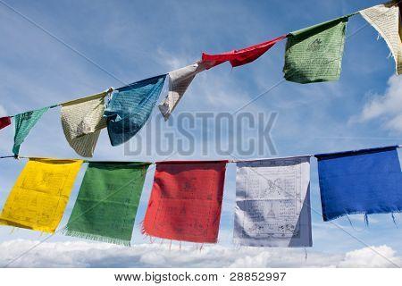 Buddhist tibetan prayer flags flying in the wind against blue sky