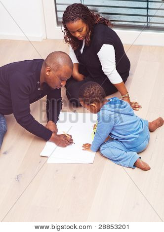 Young black family sitting on the floor drawing a picture with their son.