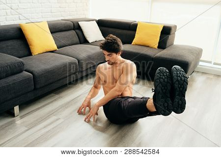 Adult Man Training Abs Muscles At Home Doing Russian Twist Exercise