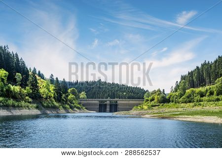 Dam In A Colorful Landscape In The Summer On A Lake Surrounded By Forest