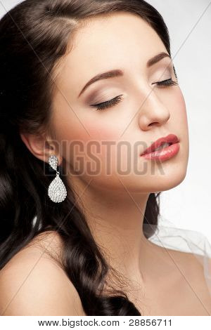 Portrait of beautiful woman with beautiful make-up and hairstyle. Elegant woman with diamond earring