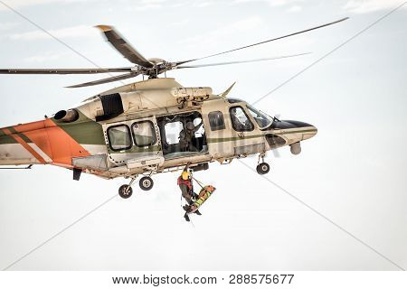 Rescue Helicopter In Flight Winching Rescuer. Color Tone Tuned