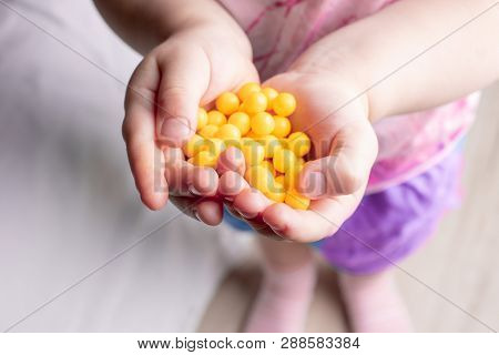 Drops of ascorbic acid in the open child's palm. the child holds pills vitamin C in hands poster