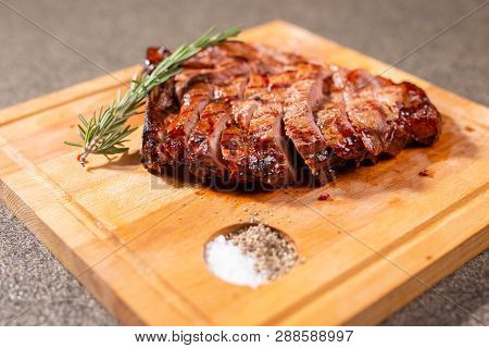 Food And Horse Meat Concept - Roast Meat On Cutting Board With Cumin