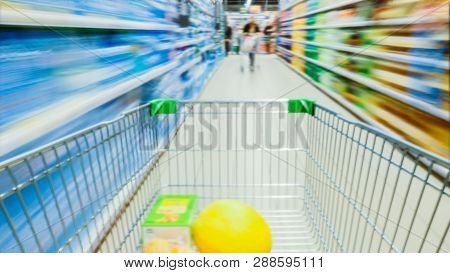 Time Lapse Of The Shopping Cart Moving Between Various Aisles And Section In The Big Supermarket. In