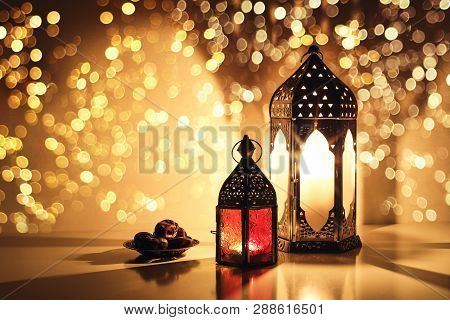 Ornamental Arabic Lanterns With Burning Candles. Glittering Golden Bokeh Lights. Plate With Date Fru