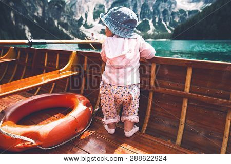Little Baby Child With Family On Walk By Traditional Wooden Boat With Oars On Braies Lake With Alpin