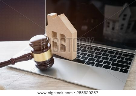 Online Auction For Real Estate Concept. Judge Gavel And House Model On Notebook Computer. Ideas For