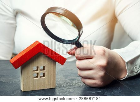 A Woman Is Holding A Magnifying Glass Over A Wooden House. Real Estate Appraiser. Assessment Of The